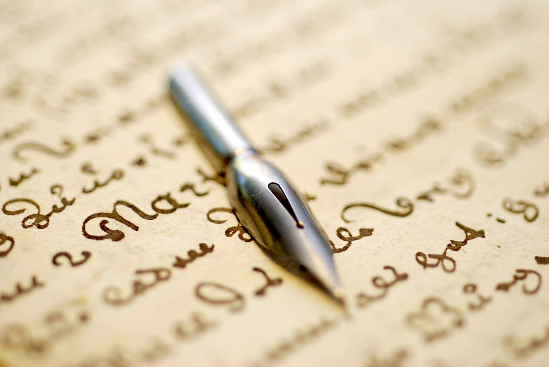 réécriture de chanson : une plume posée sur un papier