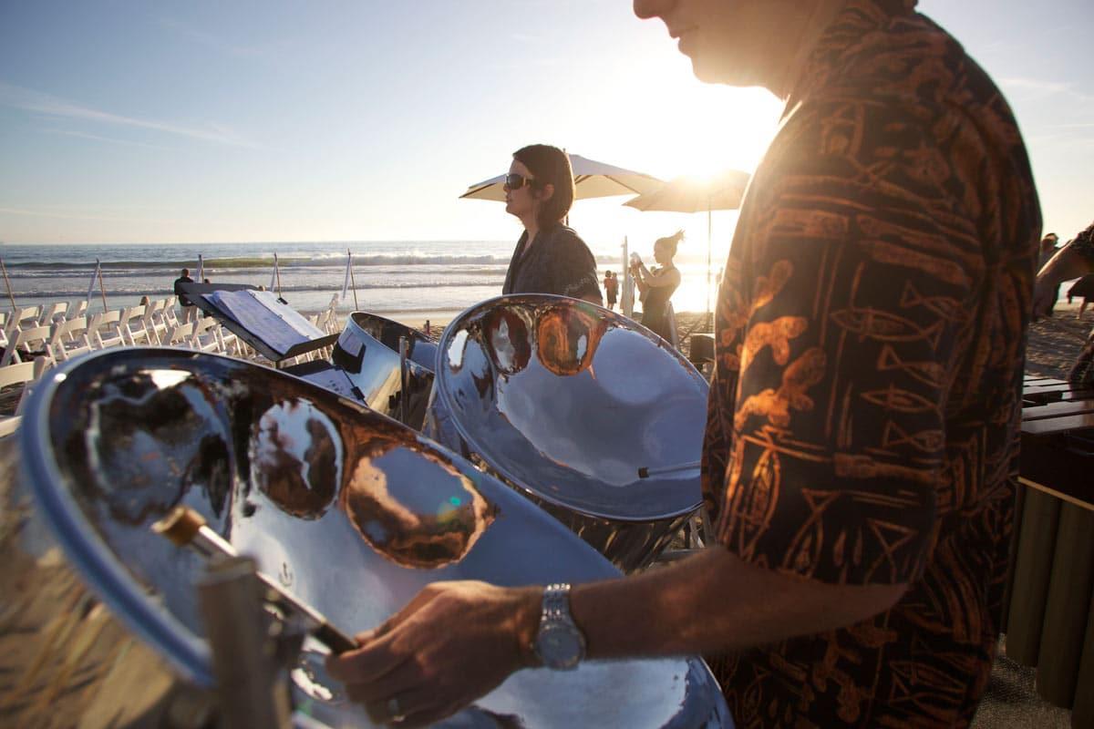 sur une plage, des musiciens jouent du steel drum